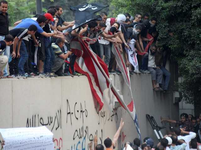 Protesters destroy an American flag pulled down from the U.S. embassy in Cairo, Egypt, Tuesday, in protest of a film deemed offensive of Islam that also resulted in the death of the Libya ambassador and three employees.