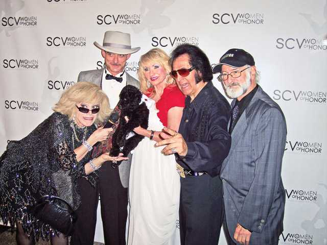 Celebrity impersonators interview Mary Ellen Bloomingdale and the black standard poodle up for auction.