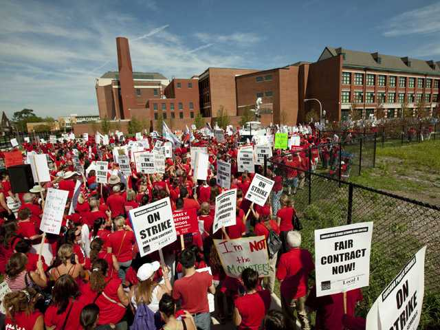 A large group of public school teachers marches past John Marshall Metropolitan High School on Wednesday in West Chicago.