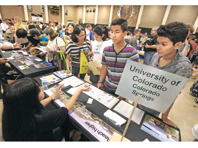 West Ranch High School students Joey Nazario, 18, center, and Ramon Gutierrez, 18, right, join thousands of students and parents as they get information at the College & Career Fair held at Golden Valley High School in Santa Clarita on Thursday.