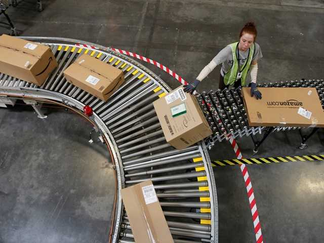 Katherine Braun sorts packages toward the right shipping area at an Amazon.com fulfillment center in Goodyear, Ariz. Products are flying off the shelves at Amazon warehouses across the county as Californians prepare to start paying sales taxes on online purchases.