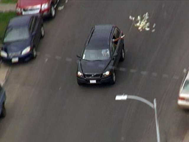 This image provided by KNBC-TV shows bank robbery suspects throwing money from their vehicle during a police pursuit Wednesday in Los Angeles.