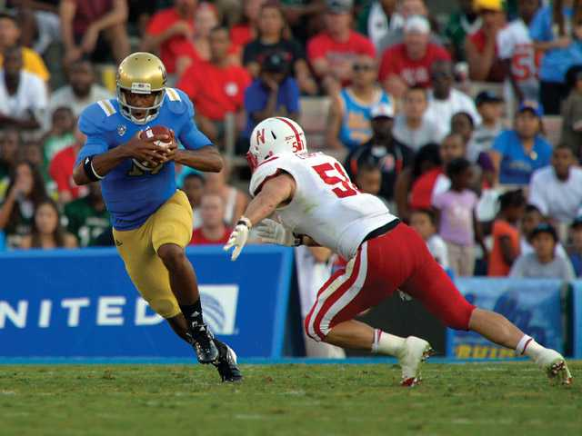 UCLA quarterback Brett Hundley, left, runs the ball as Nebraska lineman Brandon Chapek tries to tackle him during the first half of their NCAA football game on Sept. 8 in Pasadena.