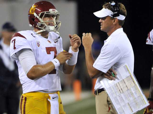 USC head coach Lane Kiffin, right, talks with quarterback Matt Barkley during the fourth quarter of an NCAA college football game against Syracuse on Sept. 8 in East Rutherford, N.J. USC defeated Syracuse 42-29.