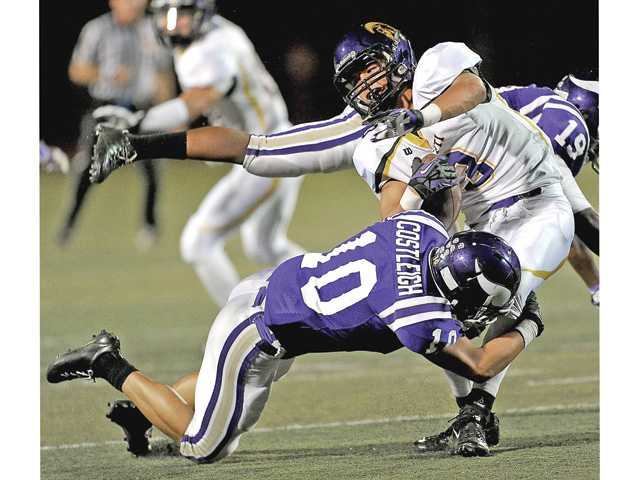 Valencia linebacker Anthony Costleigh (10) stops Righetti's Luke Wilson for a loss on Friday at Valencia High School in the Vikings' 48-9 win.