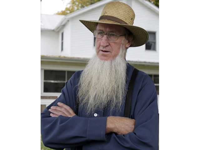 In this Oct. 10, 2011 file photo, Sam Mullet Sr. stands in the front yard of his home in Bergholz, Ohio. At the root of Amish hair-cutting attacks in Ohio was a decision by Amish bishops to overrule Mullet, the leader of a breakaway group who had shunned his former followers.
