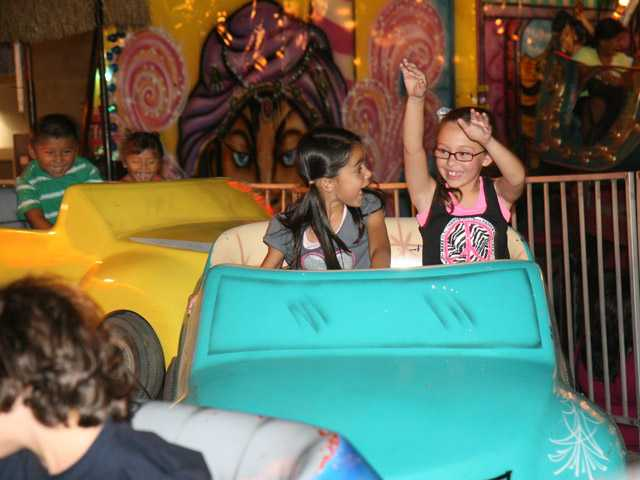 From left, Amanda Blumel, 7, and Mia Tomilin, 7, both of Newhall, enjoy a ride at the Our Lady of Perpetual Help barbecue and carnival in Newhall.