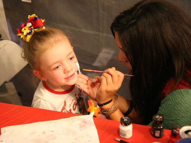 Alexia Ibarra, 14, paints the face of Marilyn Barr, 3, of Newhall, at Our Lady of Perpetual Help's carnival and barbecue on Friday.