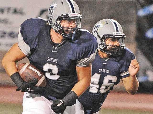 Saugus' Denley Rodriguez (9) runs back an interception while teammate Miguel Sanchez (46) runs to his side on Friday at College of the Canyons.