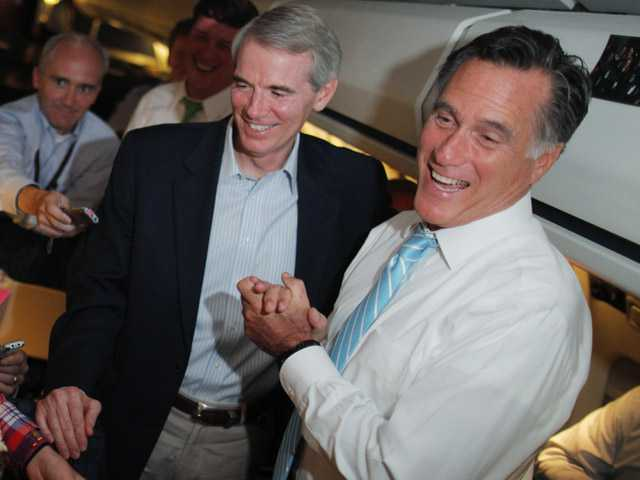 Republican presidential candidate and former Massachusetts Gov. Mitt Romney and Sen. Rob Portman, R-Ohio, talk to reporters on board the campaign charter plane as it flies to Bedford, Mass., on Friday.