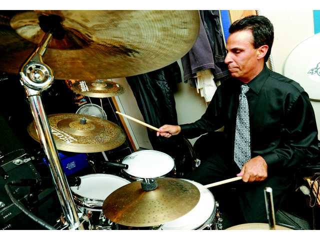Carnelli plays his drums in the studio in his Canyon Country home.