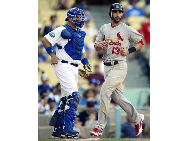 St. Louis Cardinal Matt Carpenter scores as Los Angeles Dodgers catcher A.J. Ellis watches on Sunday in Los Angeles.