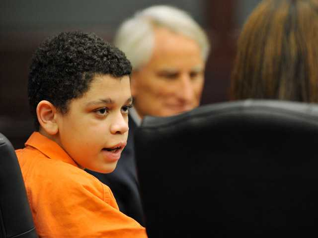 Cristian Fernandez, 13, left, talks with his attorneys in Judge Mallory Cooper's courtroom in Jacksonville, Fla.