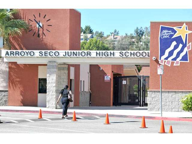 An unidentified woman walks into Arroyo Seco Junior High School in Saugus on Tuesday. The campus along with nearby Santa Clarita Elementary School remained open.