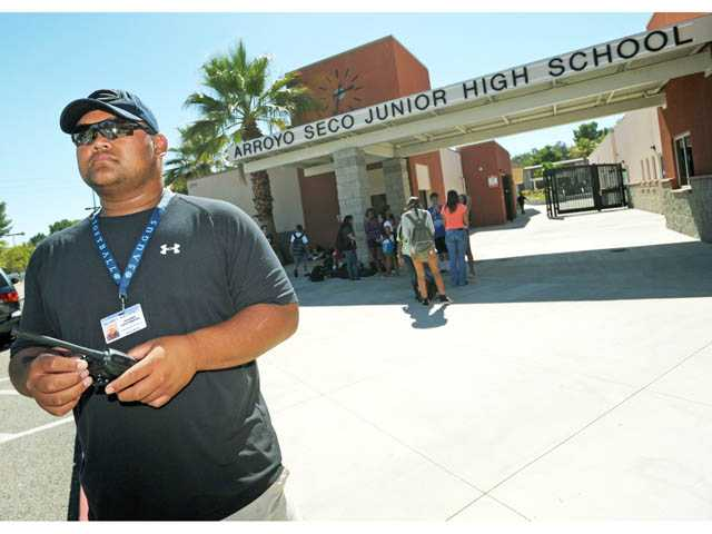 Campus supervisor Jerome Castaneda monitors the parking lot following dismissal at Arroyo Seco Junior High School in Saugus on Tuesday.