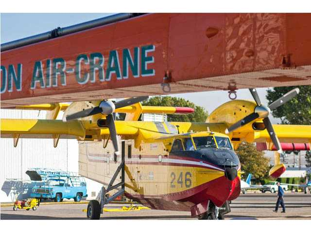 Framed by an Erickson Air Crane, a SuperScooper air tanker prepares for takeoff Friday afternoon at Van Nuys Airport.