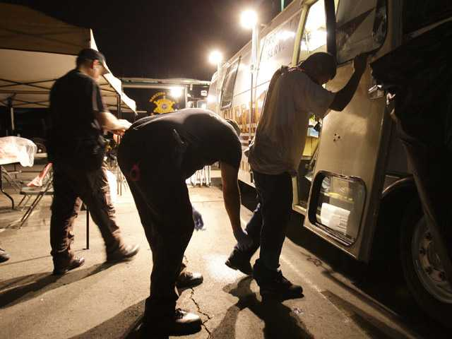 In this July 29, 2010 file photo, Maricopa County Sheriff's deputies, left, check the shoes of a suspect arrested during a crime suppression sweep in Phoenix.