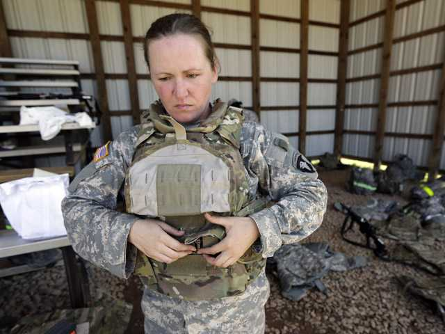 Spc. Sarah Sutphin removes her new body armor after training on a firing range on Tuesday in Fort Campbell, Ky.