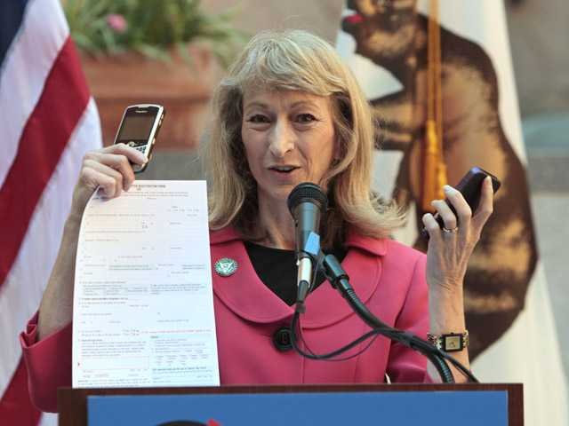 Secretary of State Debra Bowen demonstrates the different ways California voters register to vote during a conference Wednesday in Sacramento.