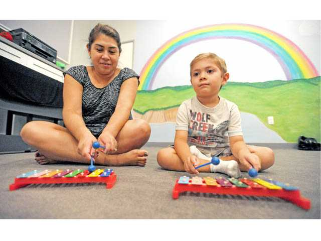 Lorena Esparza, of Valencia, and son Matthew, 4, play glockenspiels at the Little School of Music in Valencia on Tuesday.