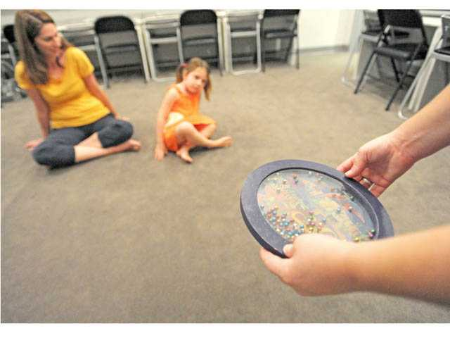 Mindy Cabral introduces the ocean drum to Amanda Williams, of Valencia, left, and daughter Audrey, 4, at the Little School of Music in Valencia on Tuesday.