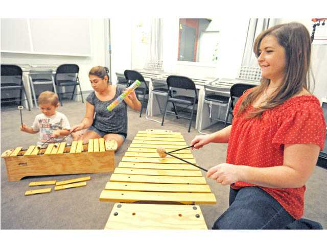 Matthew Esparza, 4, and mother Lorena, of Valencia, join Mindy Cabral in learning about the xylophone at the Little School of Music in Valencia on Tuesday.