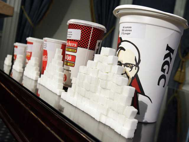 This May 31 file photo shows a display of various size soft drink cups next to stacks of sugar cubes at a news conference at New York's City Hall.