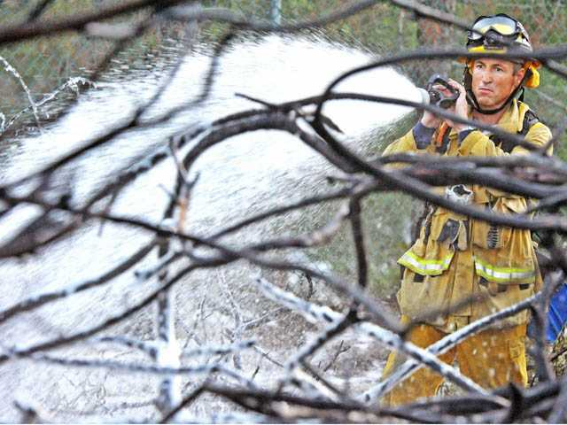 A firefighter mops up following a small brush fire at Pamplico Park in Saugus on Thursday.