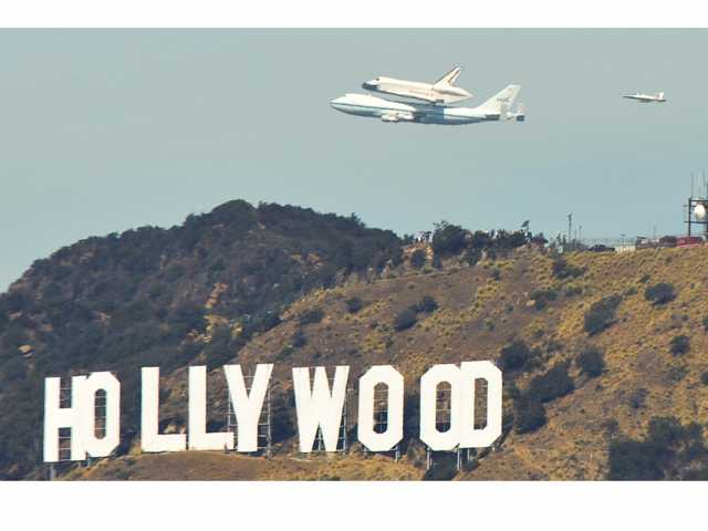 A NASA Shuttle Carrier Aircraft carries the Space Shuttle Endeavour as it flies over the Hollywood Sign, as seen from the Griffith Observatory in Los Angeles on Friday.    Jonathan Pobre/ The Signal