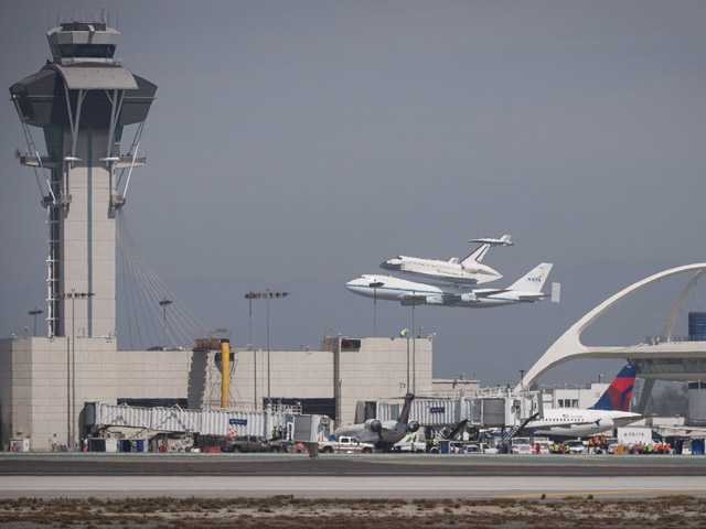 Space Shuttle Endeavour mounted atop a NASA 747 Shuttle Carrier Aircraft flies past the tower at Los Angeles International Airport, on Friday.