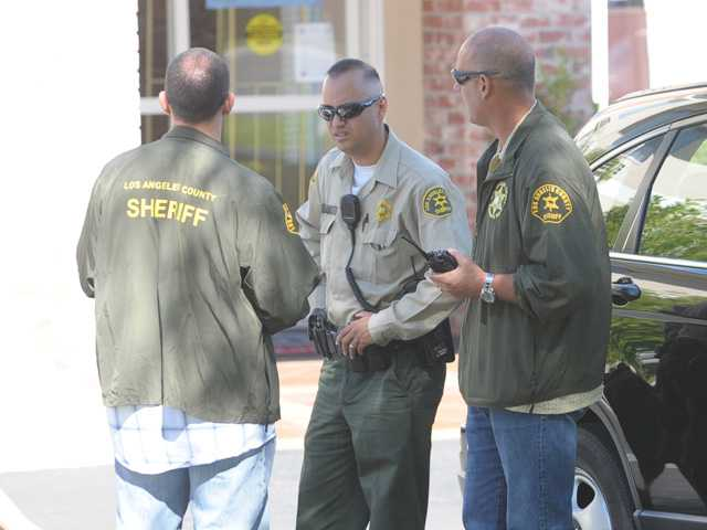 L.A. County Sheriff's deputies gather in front of the Fairfield Inn in Stevenson Ranch after it was robbed on Friday morning, the suspect escaped in a black SUV.