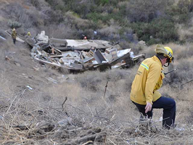 A firefighter makes his way down the mountainside toward the motor home. (Rick McClure/For The Signal)