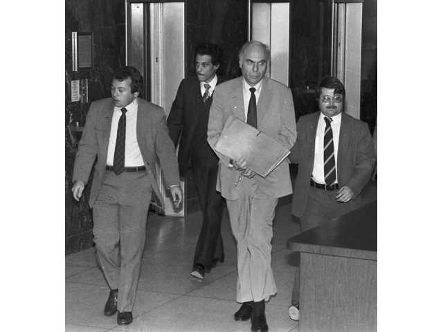 In this  1983 photo, ex-CIA agent Edwin Wilson, center, leaves federal court after a day of jury selection accompanied by U.S. Marshals in Houston.