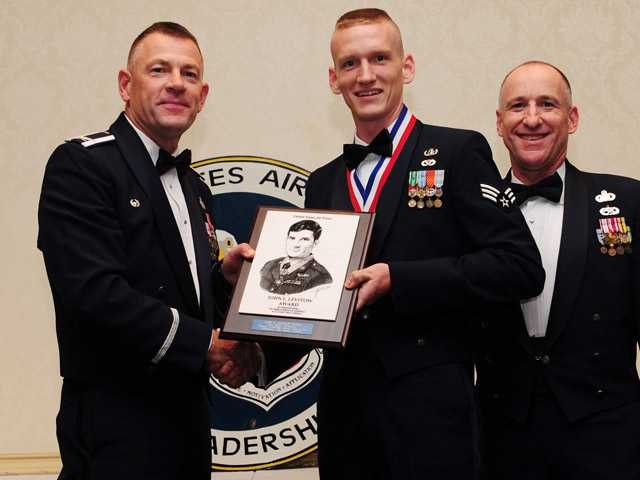 Col. Richard McComb and Chief Master Sgt. Earl Hannon present the John L. Levitow Award to Senior Airman Patrick Dougherty, center at Joint Base Charleston Air Base.