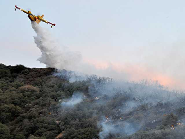 A Super Scooper plane drops water on a brush fire near Old Ridge Route Road on Saturday. (Rick McClure/For The Signal)