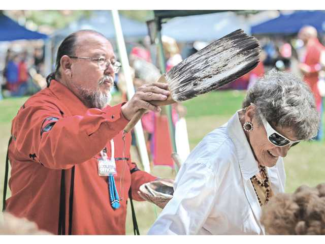 Ted Garcia, left, performs a purification ceremony using an eagle wing fan and burning sage on Elly Eisele of Canyon Country.(Dan Watson/The Signal)