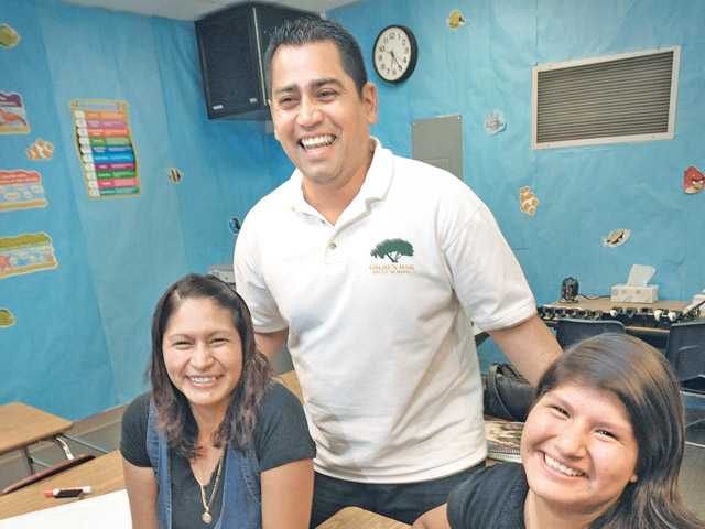 English teacher Instructor Rob Isquierdo Jr., center, with mother Elizabeth Alcibar, left, and daughter Fatima Cruz, 12, on Thursday. (Dan Watson/The Signal)