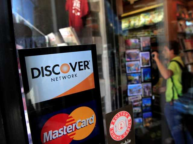 A Discover logo at a shop in Cambridge, Mass., Monday. Discover Bank is paying $214 million to settle charges that it pressured card holders to buy costly add-on services like payment protection and credit monitoring.