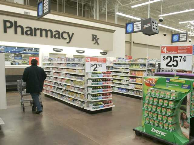 In this Feb. 20, 2008, file photo, a shopper walks toward the pharmacy at a Little Rock, Ark., Wal-Mart store.