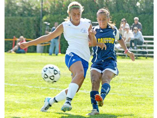 College of the Canyons defender Kassandra Talamantez, right, kicks the ball against Santa Monica College during Tuesday's game at COC.