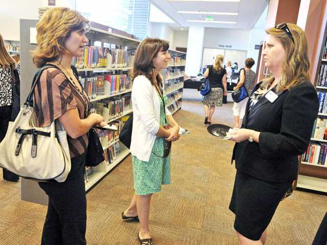 From left, teachers Julie Johnson and Michelle Vasquez speak with Allie Augusta of the Friends of the Library group during the Educator's Reception at the Old Town Newhall Library on Monday.