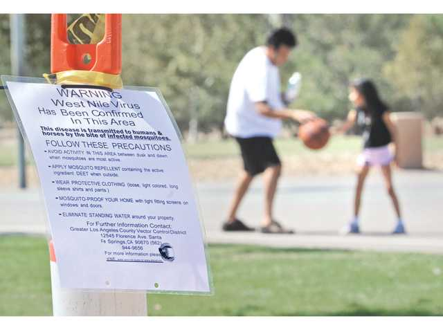 David and Valerie Blanco, 6, of Saugus play basketball next to one of nine West Nile Virus warning posters attached to orange cones at Central Park in Saugus on Wednesday listing precautions park visitors should take regarding bites from infected mosquitoes after the second person in Los Angeles County died.