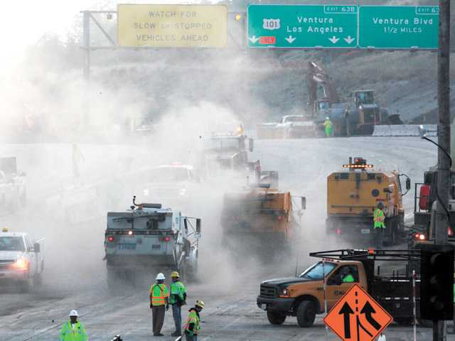 Street sweepers take over after the demolition of two lanes of the Mulholland Bridge in Los Angeles on July 17, 2011.