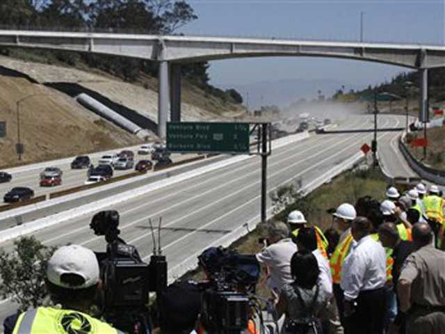 This July 17, 2011 file photo shows the California Highway Patrol leading the first vehicles on southbound Interstate 405 as demolition of a portion of the bridge is completed before noon in Los Angeles.