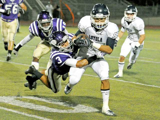 Valencia defensive back Aaren Dominguez (3) tries to take down Loyola wide receiver Mekai Sheffie on Friday night at Valencia.