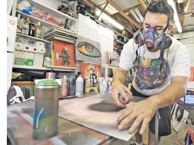 Misas dons a respirator to protect himself from fumes as he crafts his art work.
