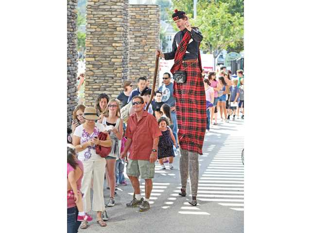 "Christopher Yates on stilts as ""McCloud"" entertains the hundreds of library visitors as they wait their turn to enter the new Newhall Public Library at the grand opening on Main Street in Newhall on Saturday."