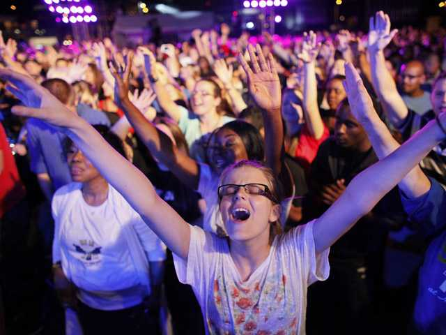 Dharma Bohall, 13, extends her arms in prayer during the America for Jesus prayer rally, Friday Sept. 28, 2012, on Independence Mall in Philadelphia.
