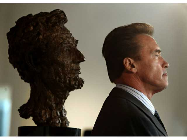 Former Gov. Arnold Schwarzenegger and a bust of Abraham Lincoln are seen in profile during a celebration of Lincoln's 200 birthday.