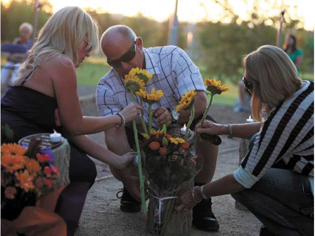 "Seika Simon, 26, left, Wayne Rhoades, middle, and Patty Rhoades, right, of Saugus pay tribute to Andrew ""Roo"" Rhoades at the Youth Grove in Central Park during the 7th Annual Evening of Remembrance on Saturday. Andrew's life was cut short at the age of 17 after a distracted driving accident 9 years ago."